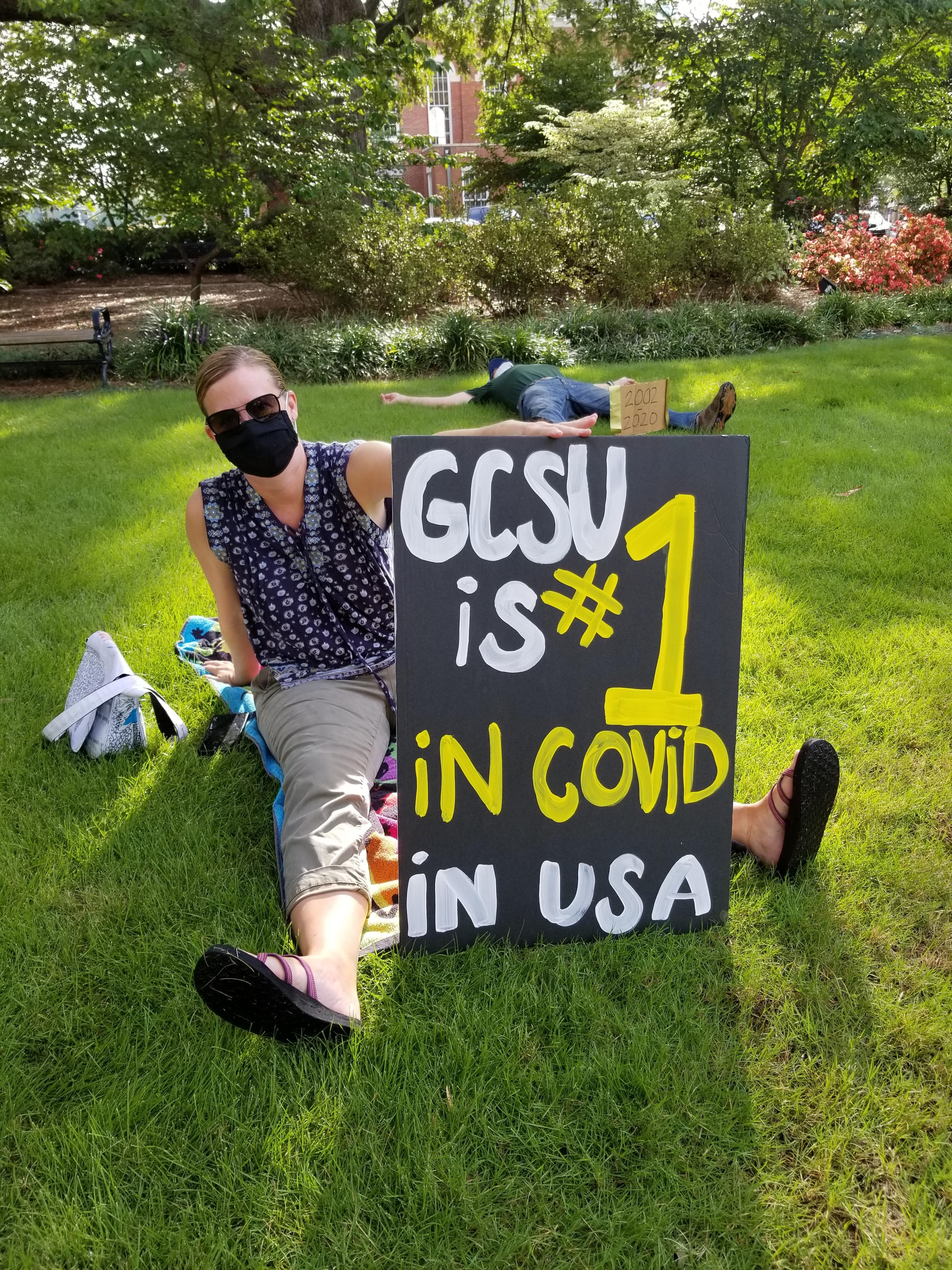 "Masked protestor holds a sign that reads ""GCSU is # 1 in COVID in USA."""