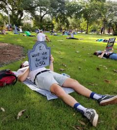 "Foreground: student lies on the grass holding a tombstone shaped sign that reads ""I won't die for the USG."" In the background, protestors lie or sit socially distanced with other signs."