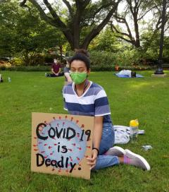 "A masked student looks into the camera with a serious expression and holding a sign that reads ""COVID-19 is deadly."" Socially distanced protestors hold signs in the background."